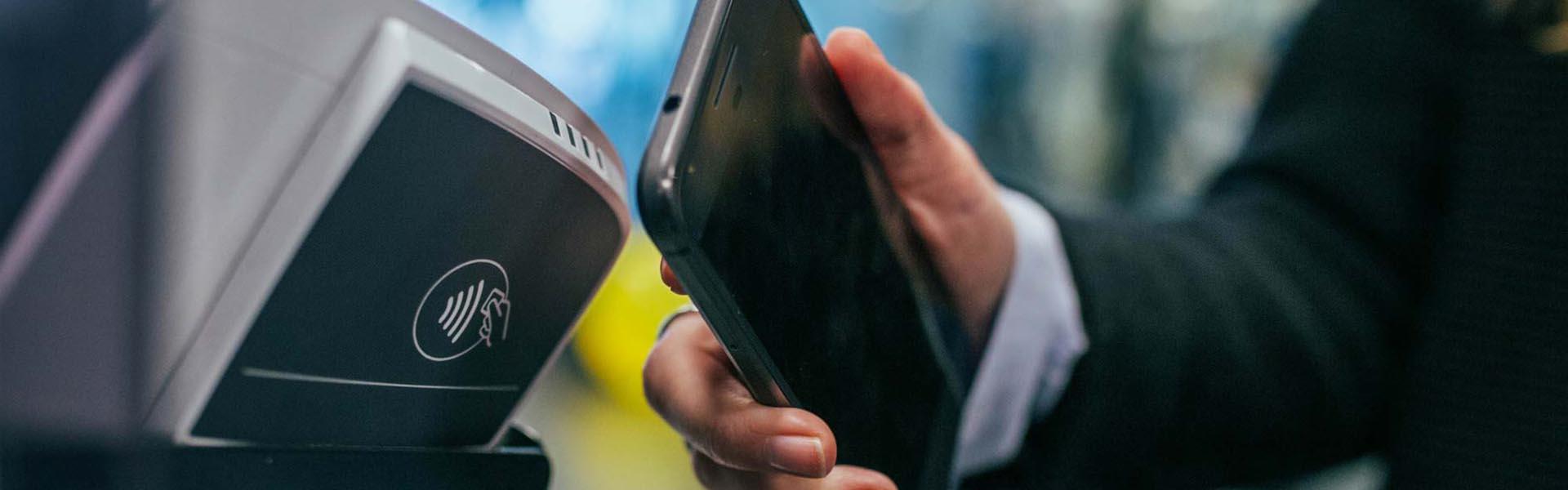 Mão de homem a segurar num smartphone enquanto passa por um gateway de pagamento