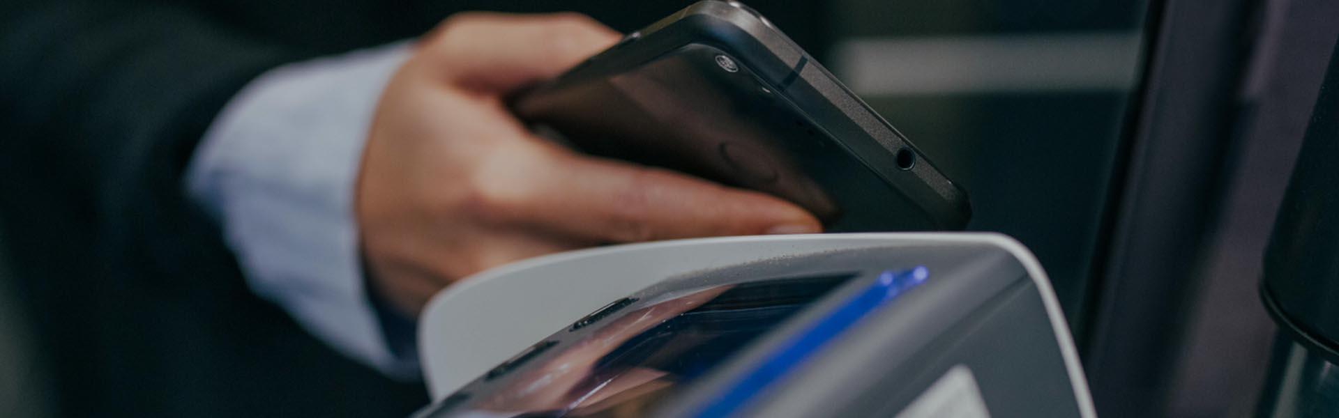 Homem de negócios a fazer um pagamento móvel através do MBWay com um smartphone