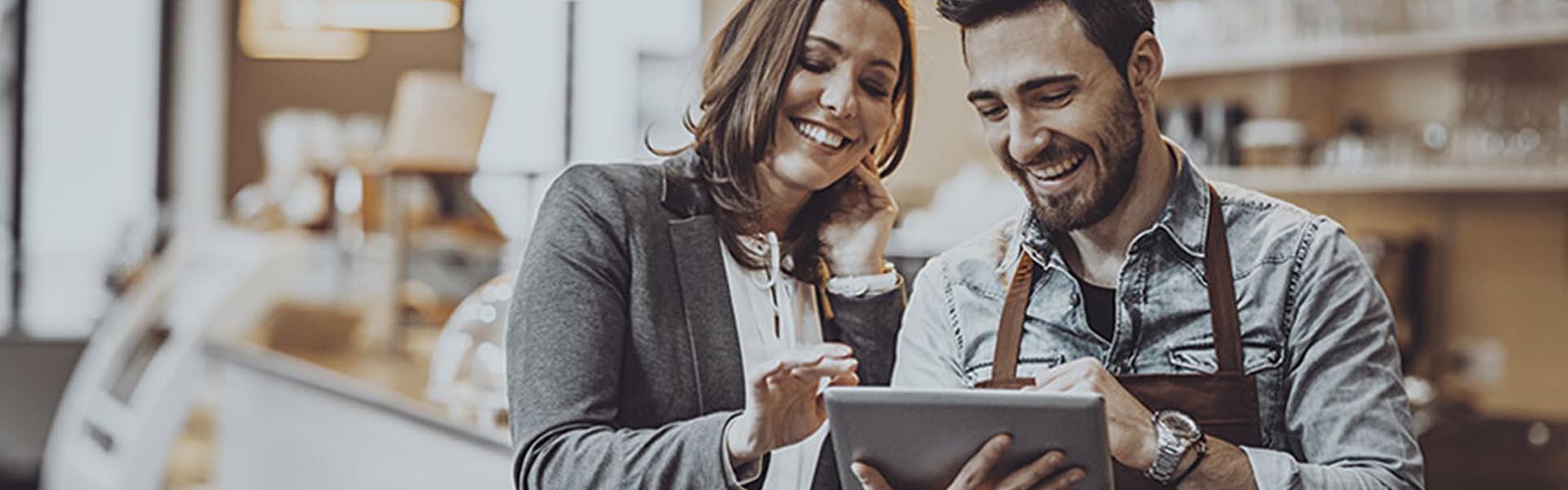 Mulher e homem a consultarem um tablet num comércio de retalho