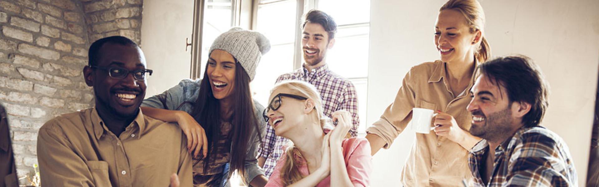 Jovens três mulheres três homens a conviver e a falar no trabalho sobre return on experience