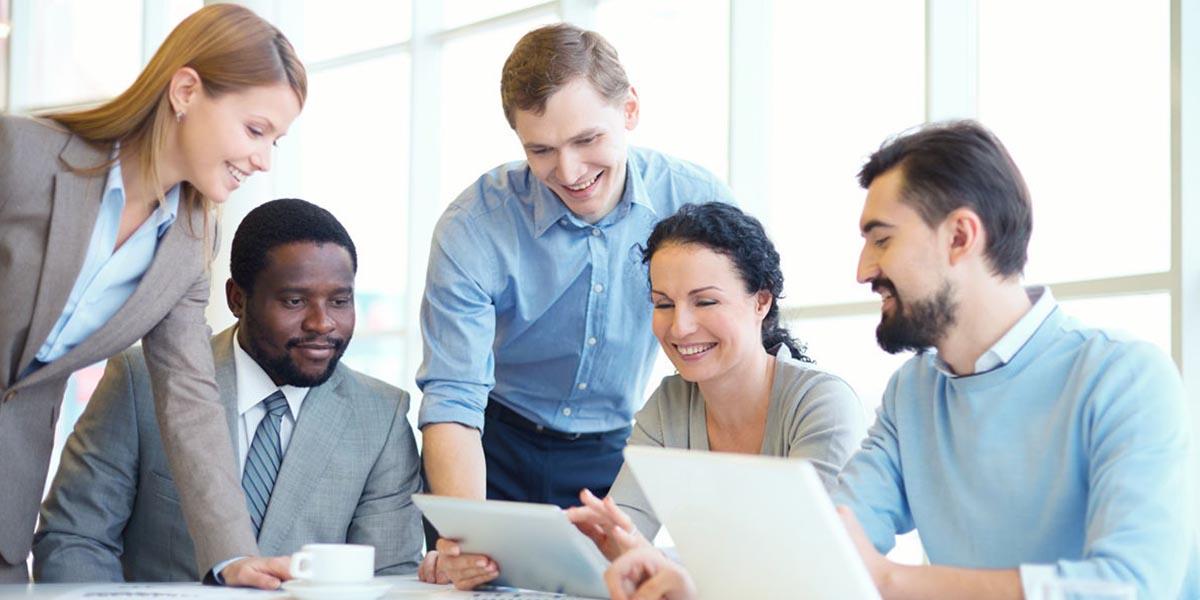 Reunião de trabalho entre três homens e duas mulheres a consultarem no tablet a boa gestão