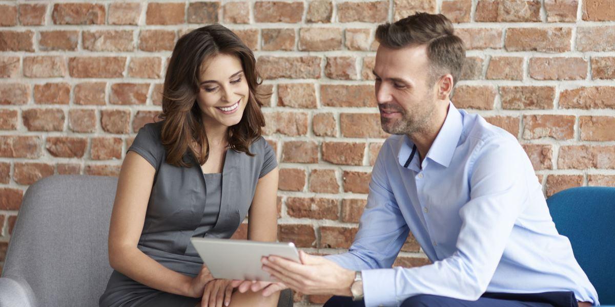 Reunião homem e mulher sobre marcação de férias com tablet