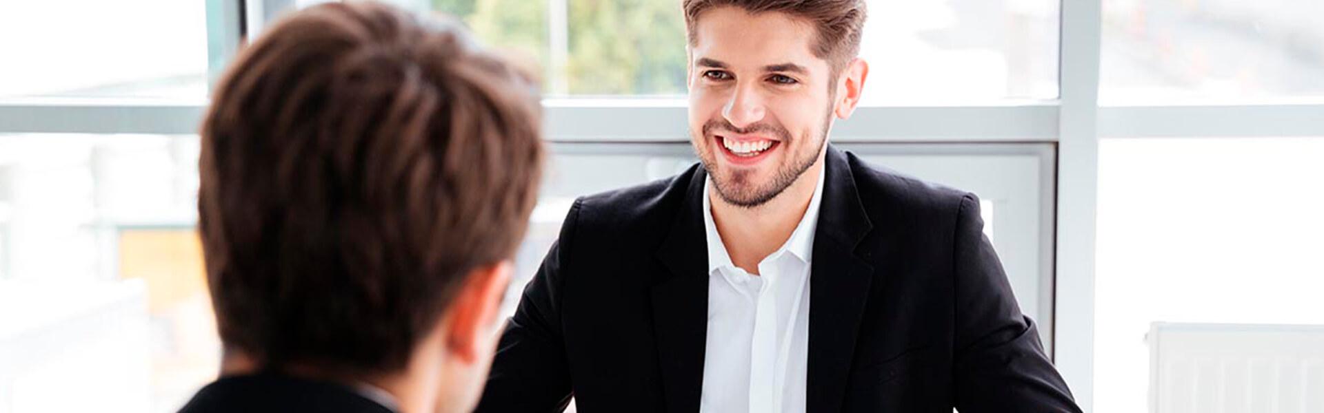 Dois homens de negócios sentados frente a frente numa reunião no escritório sobre fidelização de clientes