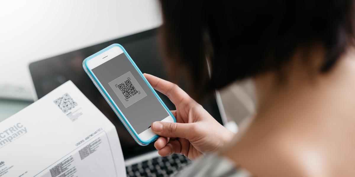 senhora a capturar o código qr de uma fatura no seu smartphone