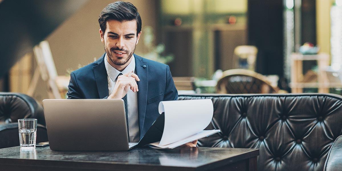Homem de negócios a consultar no portátil o regime excecional para o cumprimento das obrigações fiscais enquanto segura uma caneta e um bloco de notas