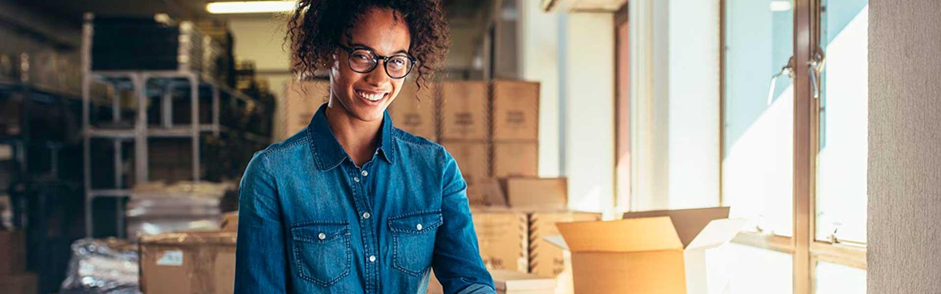 Jovem mulher empreendedora a sorrir enquanto delinea uma estratégia de vendas para o seu e-commerce