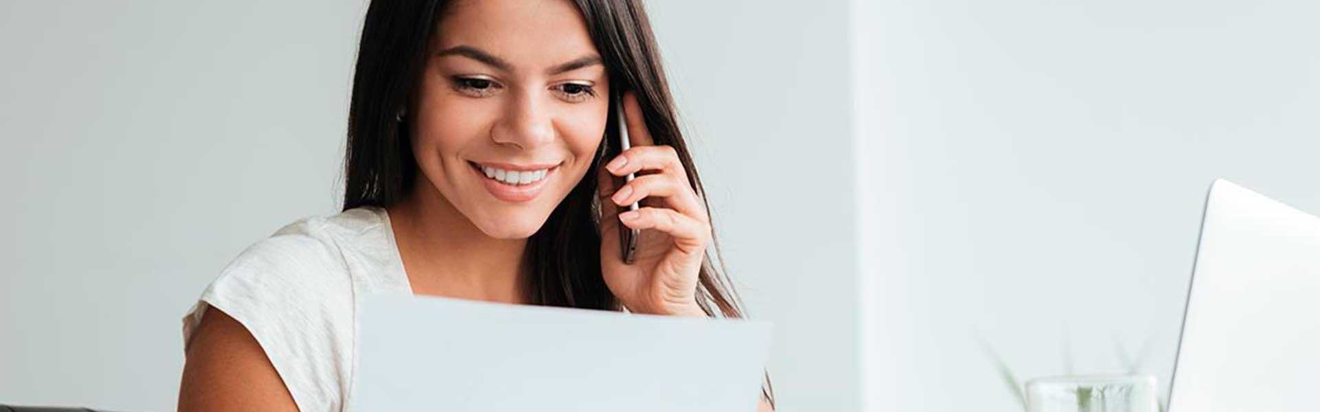 gestora a consultar a ies (Informação Empresarial Simplificada ) no papel enquanto conversa ao telemóvel e com o laptop aberto na secretária