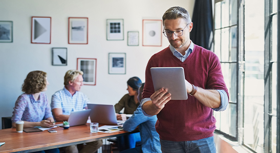 Jovem homem empresário a analisar as vendas data-driven enquanto os colegas discutem na mesa