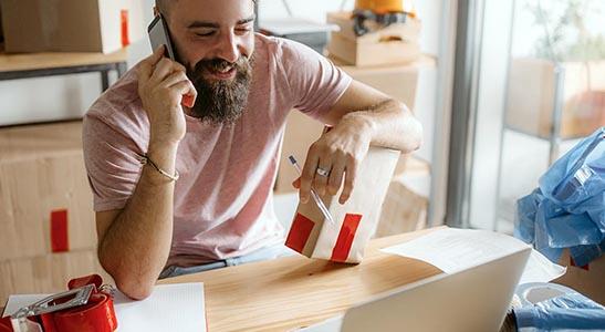Homem de negócios a tratar dos negócios da sua loja online por telefone