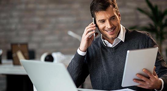 Homem de negócios a falar ao telemóvel e a fazer a gestão da contabilidade no tablet