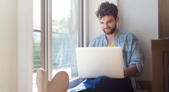 Jovem homem a consultar no laptop o futuro dos colaboradores e das empresas no trabalho remoto
