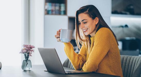 Jovem mulher a consultar no laptop as 6 formas de manter a produtividade em trabalho remoto