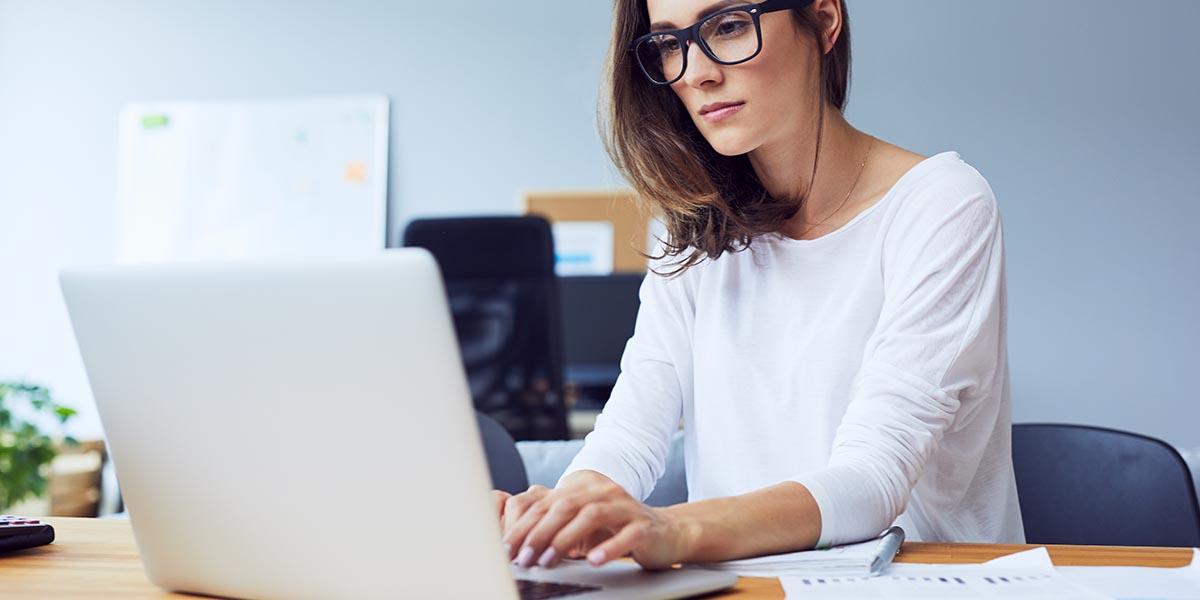 Mulher de negócios a utilizar um software de gestão de ativos no seu laptop
