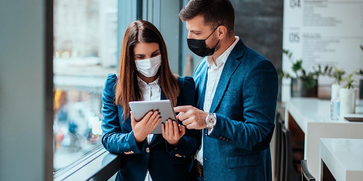 Mulher e homem de negócios a consultarem o Plano de Recuperação e Resiliência num tablet