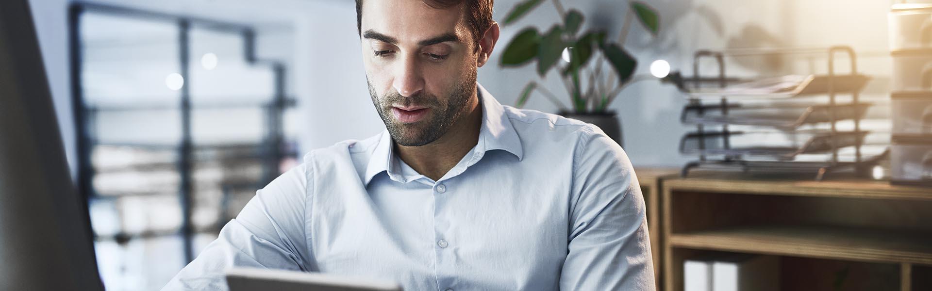 Homem de negócios sentado na secretária de trabalho a consultar a declaração modelo 22 no tablet