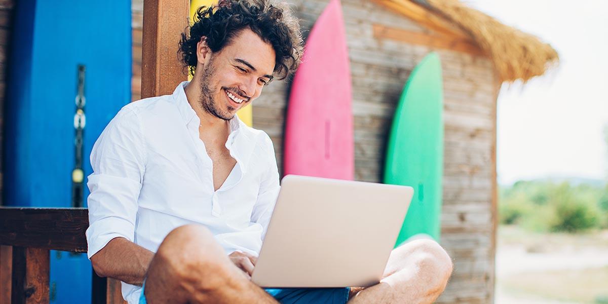 Jovem empresário na praia e a consultar no portátil o Guia prático: como tornar a minha empresa mais produtiva no verão